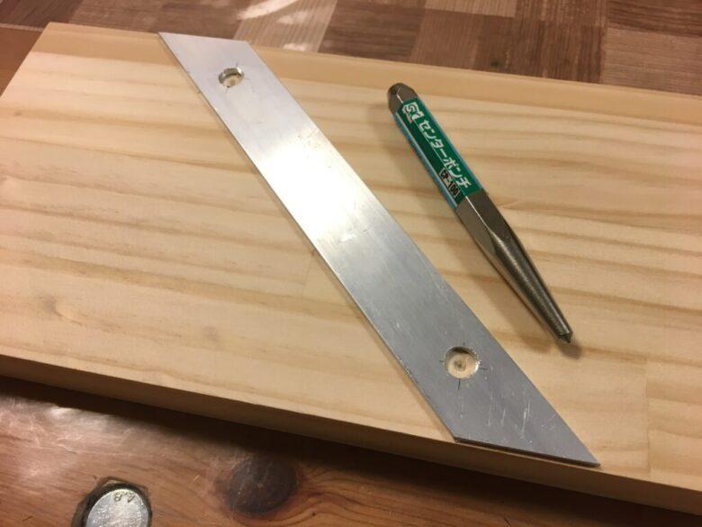 アルミ板の位置を決めたら、ベース板にもセンターポンチで印をつける